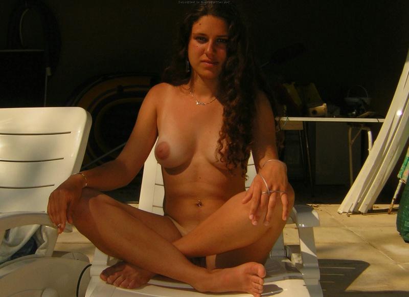 Кудрявая темненькая девушка загорает у бассейна